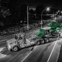 black and white and green thumbnail of 150-ton dual lane trailer carrying a compressor package turning on a road in British Columbia at night