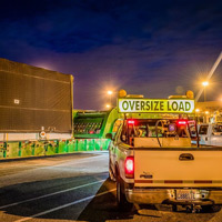 full color thumbnail of compressor package sitting on 150-ton dual lane trailer alongside oversize load crew at night