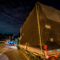 full color thumbnail of compressor package sitting on 150-ton dual lane trailer at night