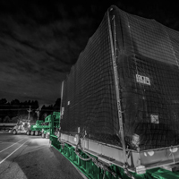 black and white and green thumbnail of compressor package sitting on 150-ton dual lane trailer at night