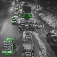 black and white and green thumbnail of Omega Morgan 150-ton dual lane trailer carrying compressor package with push truck and supporting vehicles on the road at night