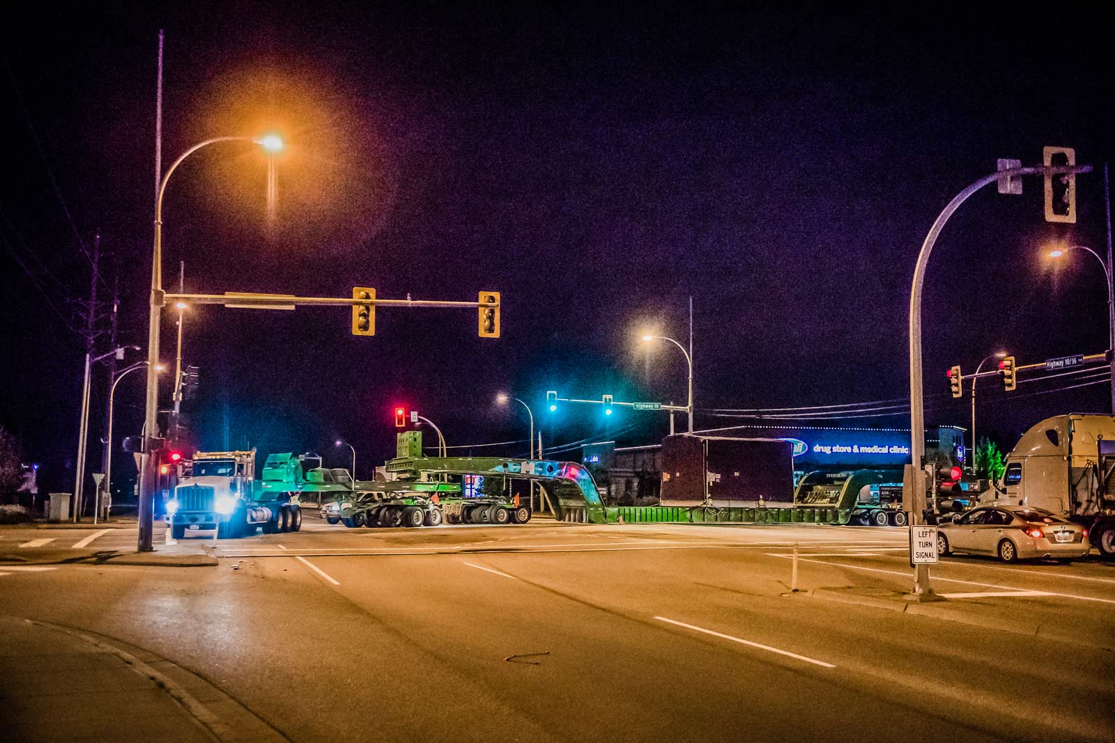 150-ton dual lane trailer carrying compressor package turning at an intersection in British Columbia at night