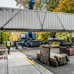Omega Morgan Sarens crane lifting a large powerhouse over a sidewalk in front of Good Samaritan hospital near Seattle, Washington