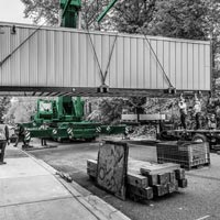 deselected thumbnail button of Omega Morgan Sarens crane lifting a large powerhouse over a sidewalk in front of Good Samaritan hospital near Seattle, Washington