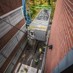 Omega Morgan Sarens crane placing a new power house in a tight space between two brick walls at Good Samaritan hospital