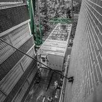 deselected thumbnail button of Omega Morgan Sarens crane placing a new power house in a tight space between two brick walls at Good Samaritan hospital