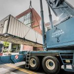 Omega Morgan Sarens logo on side of crane lifting a power plant into Good Samaritan Hospital near Seattle, Washington