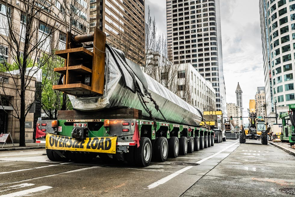 An Omega Morgan SPMT carrying an oversize load in a downtown area with skyscrapers in the background