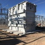 Wires above and around a large transformer in place on a cement pad.