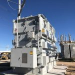 A large gray transformer on a cement pad.