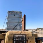 A yellow tank in front of the transformer that is secured to the railcar for transport.