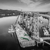 deselected thumbnail button of Omega Morgan millwrights working on Spout number one at the Kalama international grain terminal, view from the sky looking down at the dock