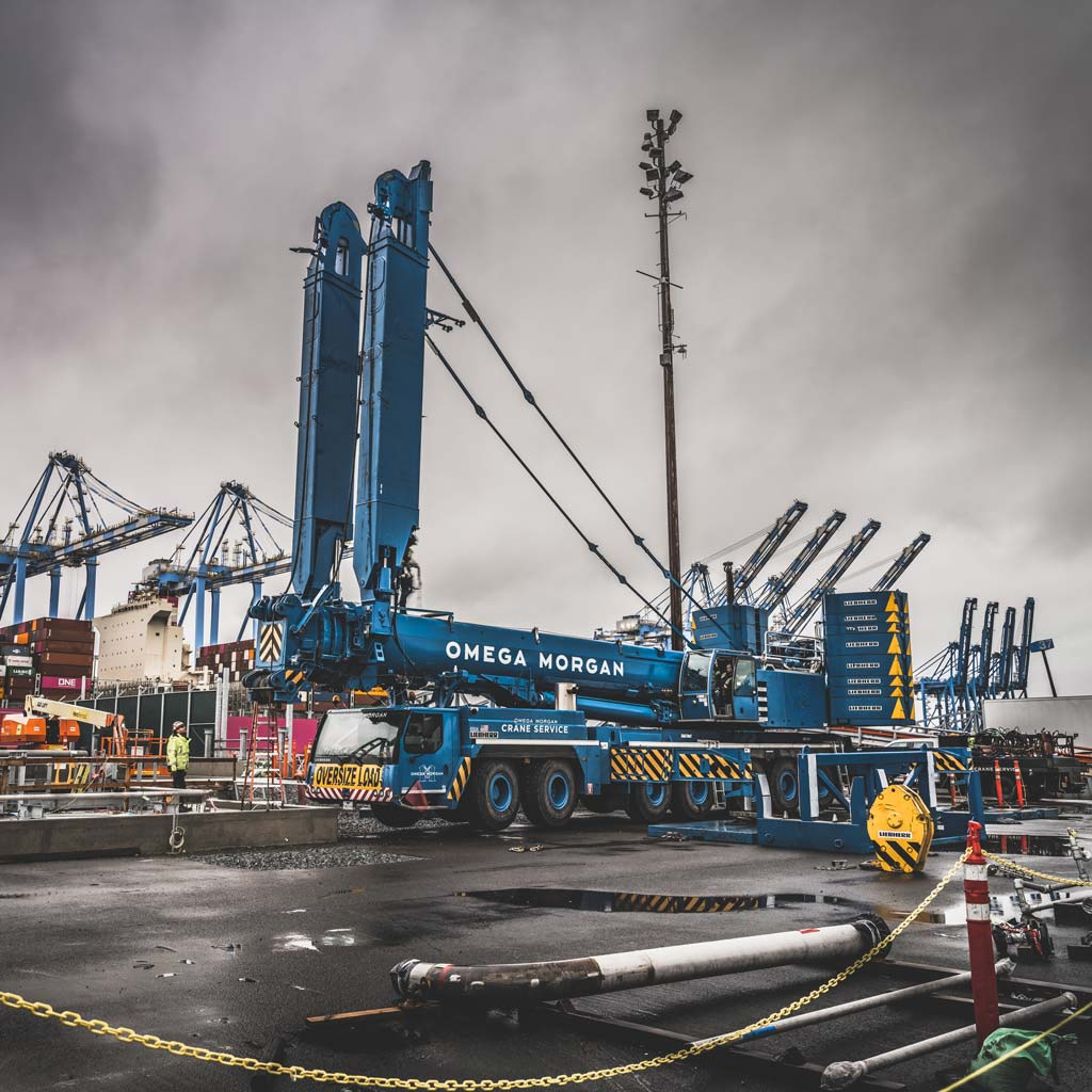 blue branded omega morgan leibherr crane with y-guy and counterweights arriving onsite at Puget Sound Energy