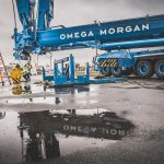 an Omega Morgan branded Liebherr L T M 1400 crane at Puget Sound Energy site with a puddle reflecting the logo
