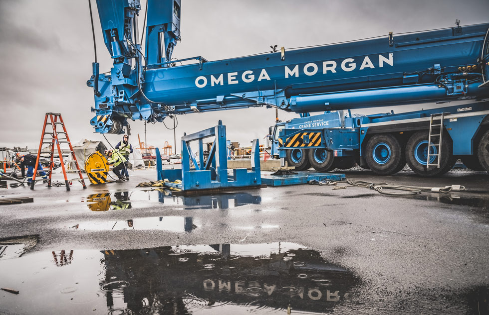 Omega Morgan crane services branded crane at Puget Sound Energy site with a puddle reflecting the logo