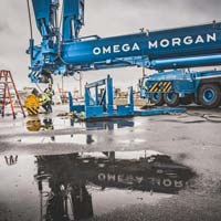 selected thumbnail button of an Omega Morgan branded Liebherr L T M 1400 crane at Puget Sound Energy site with a puddle reflecting the logo