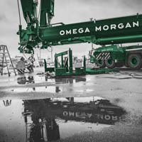 deselected thumbnail button of an Omega Morgan branded Liebherr L T M 1400 crane at Puget Sound Energy site with a puddle reflecting the logo