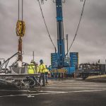 Omega Morgan crane services crew working in front of Leibherr crane onsite at Puget Sound Energy on a cloudy day