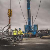 selected thumbnail button of Omega Morgan crane services crew working in front of Leibherr crane onsite at Puget Sound Energy on a cloudy day