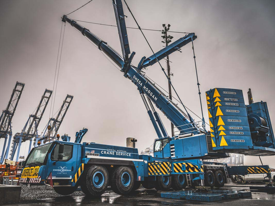 An Omega Morgan Crane Services Leibherr L T M 1400-7.1 with 308,000 pound counter weight and y-guy extended and ready for a load on a dark cloudy day