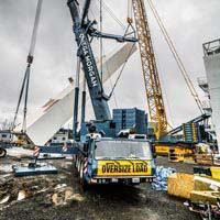 Full color thumbnail of Linde Cold Box being tilted up into place by sarens and omega morgan cranes. In the foreground the front of the omega morgan crane cab reads