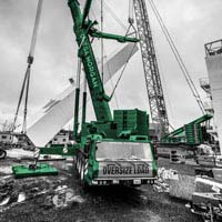 Black and white and green thumbnail of Linde Cold Box being tilted up into place by sarens and omega morgan cranes. In the foreground the front of the omega morgan crane cab reads