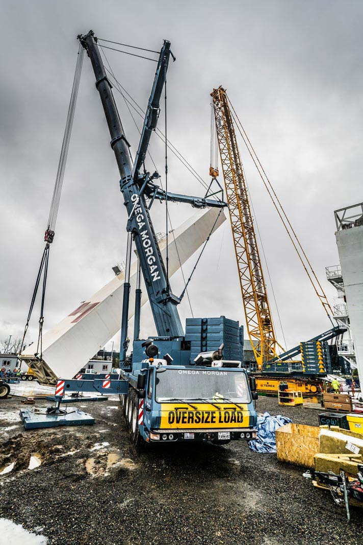 Linde Cold Box being tilted up into place by sarens and omega morgan cranes. In the foreground the front of the omega morgan crane cab reads