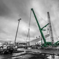 black and white and green thumbnail of two cranes lifting up a a coldbox to set it upright