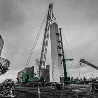 black and white and green thumbnail of two cranes setting a coldbox upright