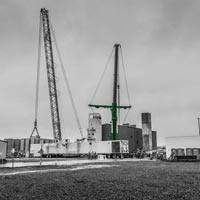 black and white and green thumbnail of cold box on its side with two cranes ready to lift and set it in place