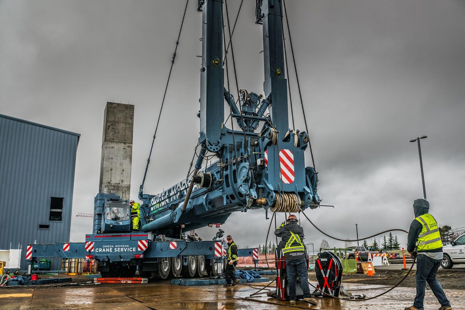 Crews setting up blue Omega Morgan crane