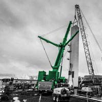 black and white and green thumbnail of cranes lifting and setting a cold box into place