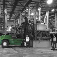 deselected thumbnail button of Omega Morgan Millwright crew of four moving equipment inside of the previous GCL Growers Warehouse in Portland
