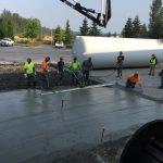 Omega Morgan millwright team members standing over a slap of freshly poured concrete at the GCL Growers old warehouse site