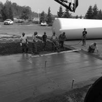 deselected thumbnail button of Omega Morgan millwright team members standing over a slap of freshly poured concrete at the GCL Growers old warehouse site