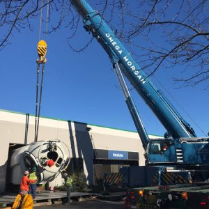 crews with blue omega morgan crane lifting nacelle into building