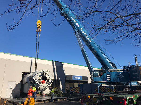 crews with blue omega morgan crane lifting nacelle into building
