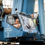 cab of blue Omega Morgan crane with operator inside at Seattle job site