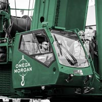 deselected thumbnail button of cab of blue Omega Morgan crane with operator inside at Seattle job site