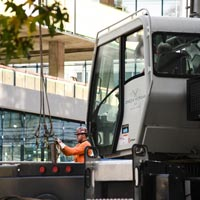 selected thumbnail button of crane crewmember working with hoist behind a crane in front of the newly constructed 1818 Fairview building in Seattle Washington