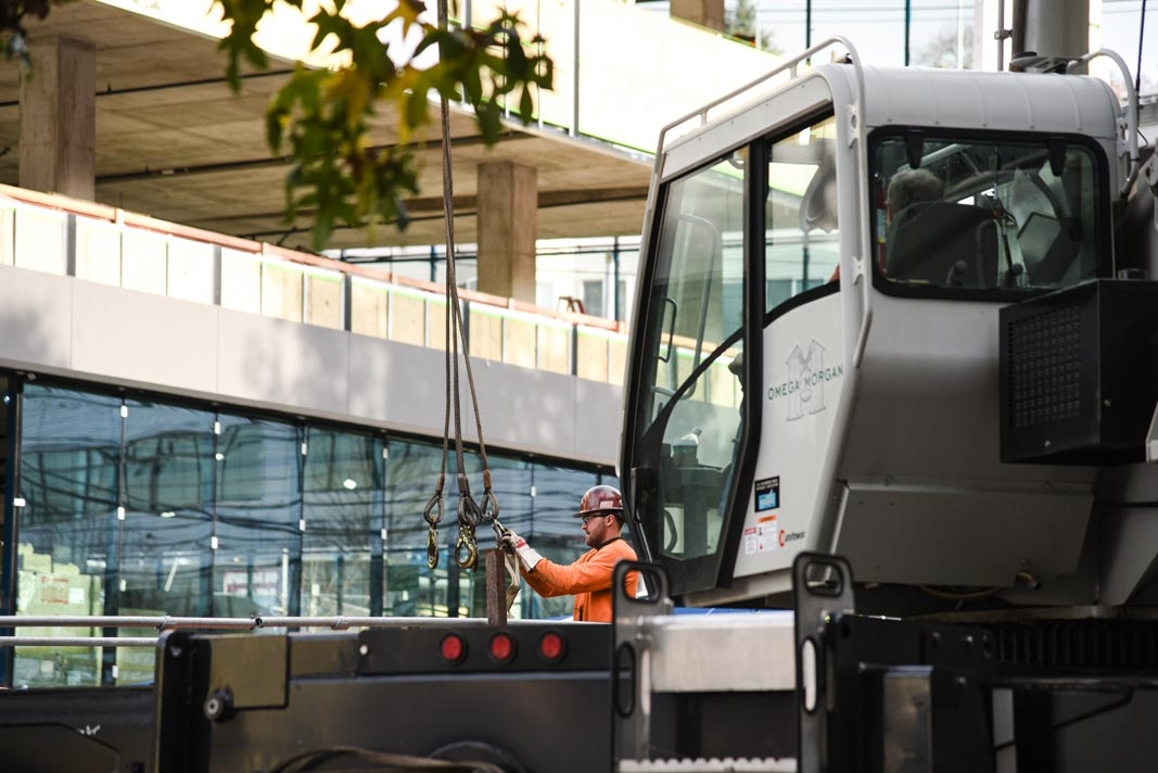 crane crewmember working with hoist behind a crane in front of the newly constructed 1818 Fairview building in Seattle Washington