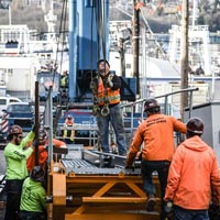 selected thumbnail button of five crane workers working at the base of a crane at the 1818 Fairview building construction site in downtown Seattle Washington