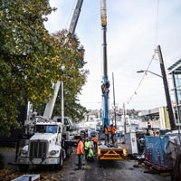 selected thumbnail button of crane team crew members working in a narrow street with two cranes in front of 1818 fairview building in seattle washington