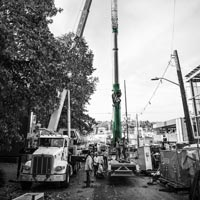 deselected thumbnail button of crane team crew members working in a narrow street with two cranes in front of 1818 fairview building in seattle washington