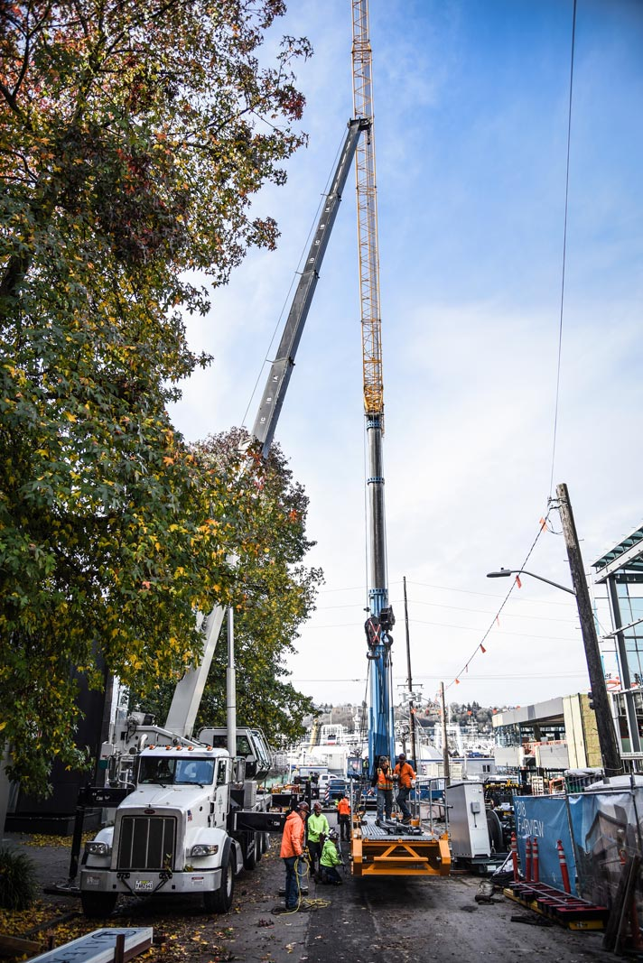 crane team crew members working in a narrow street with two cranes in front of 1818 fairview building in seattle washington
