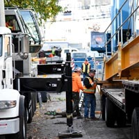 selected thumbnail button of crane team on the ground between two cranes in a tight street while crane operators in cabs look on in downtown seattle, washington