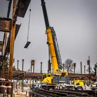 selected thumbnail button of Omega Morgan Sarens 115-ton Grove TMS9000-2 crane lifting a piece of steel for Evergreen Erectors at Mirror Lake Elementary School construction site