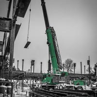 deselected thumbnail button of Omega Morgan Sarens 115-ton Grove TMS9000-2 crane lifting a piece of steel for Evergreen Erectors at Mirror Lake Elementary School construction site