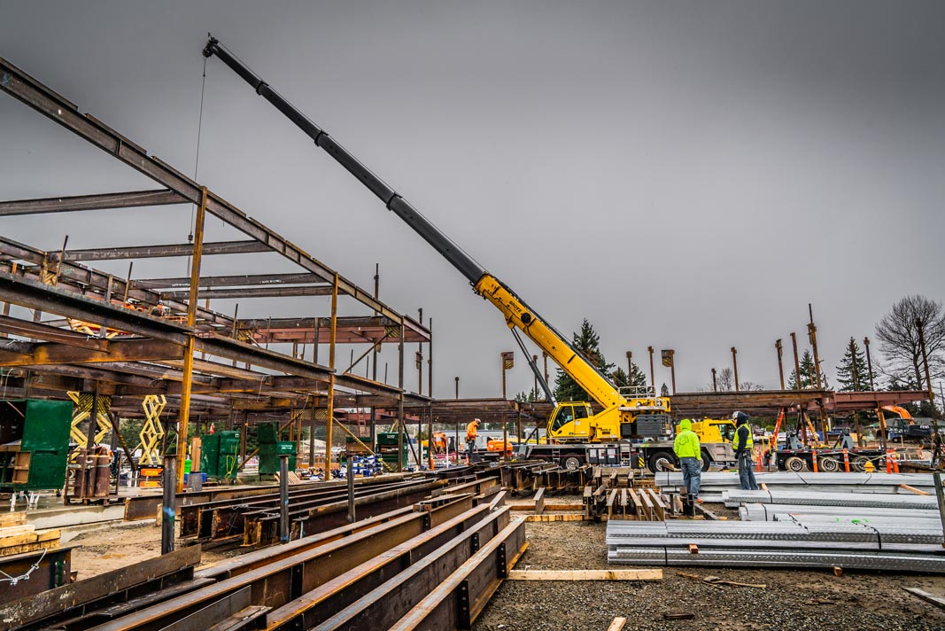 Omega Morgan Sarens 115-ton Grove TMS9000-2 crane extended out over the steel structure of the new Mirror Lake Elementary school building
