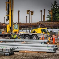 selected thumbnail button of piles of steel at the new Mirror Lake Elementary school site where Evergreen Erectors crew are preparing to hook pieces onto an Omega Morgan 115-ton Grove crane